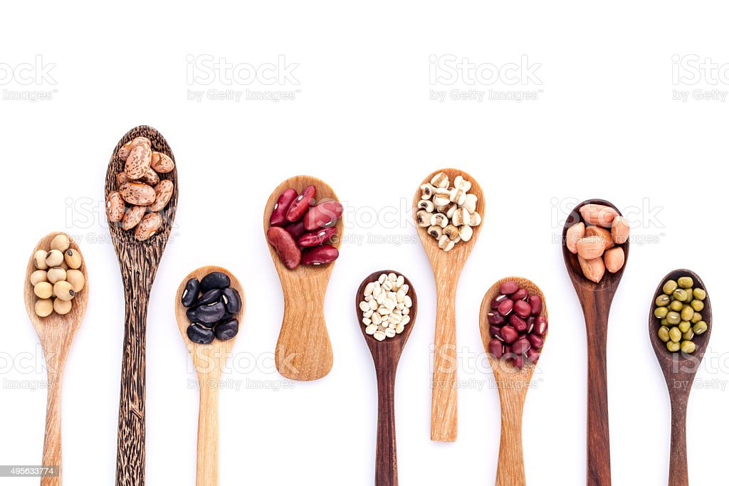 Assortment of beans and lentils in wooden spoon . stock photo