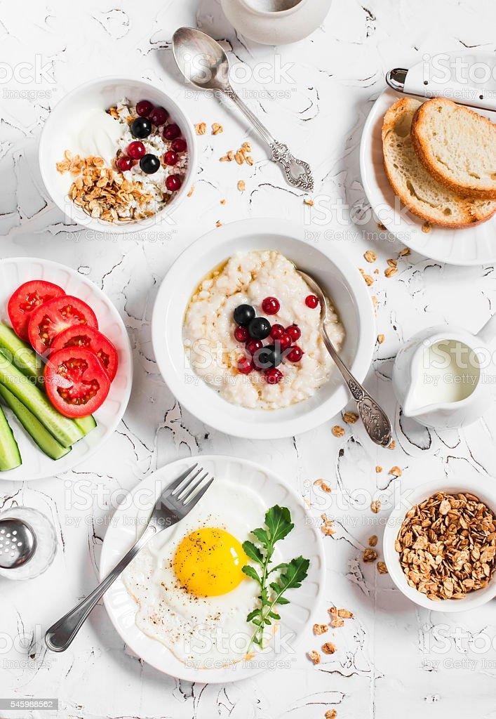 Assortment of breakfast - oatmeal, egg, vegetables, cottage cheese, yogurt stock photo