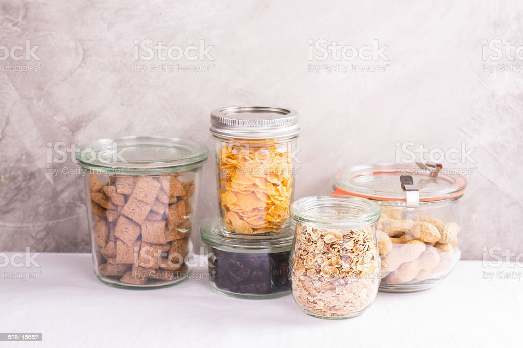 Assortment of cereals and nuts in storage jars stock photo