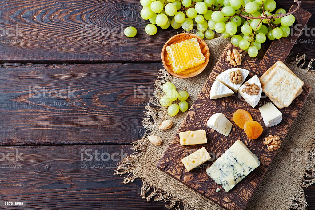 Assortment of cheese with honey, nuts and grape stock photo