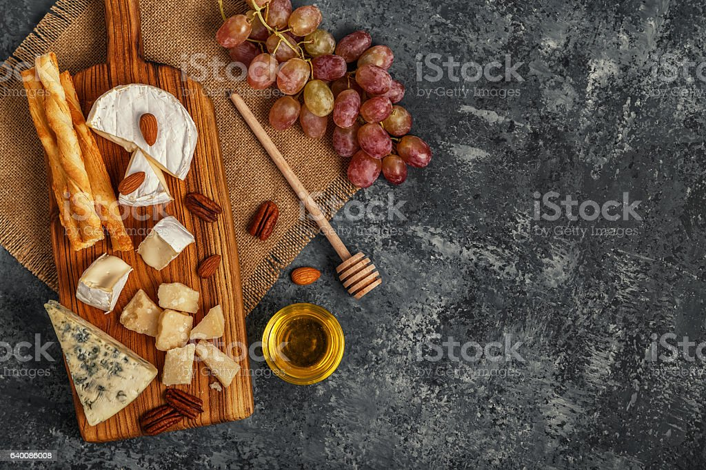 Assortment of cheese with honey, nuts and grape. stock photo