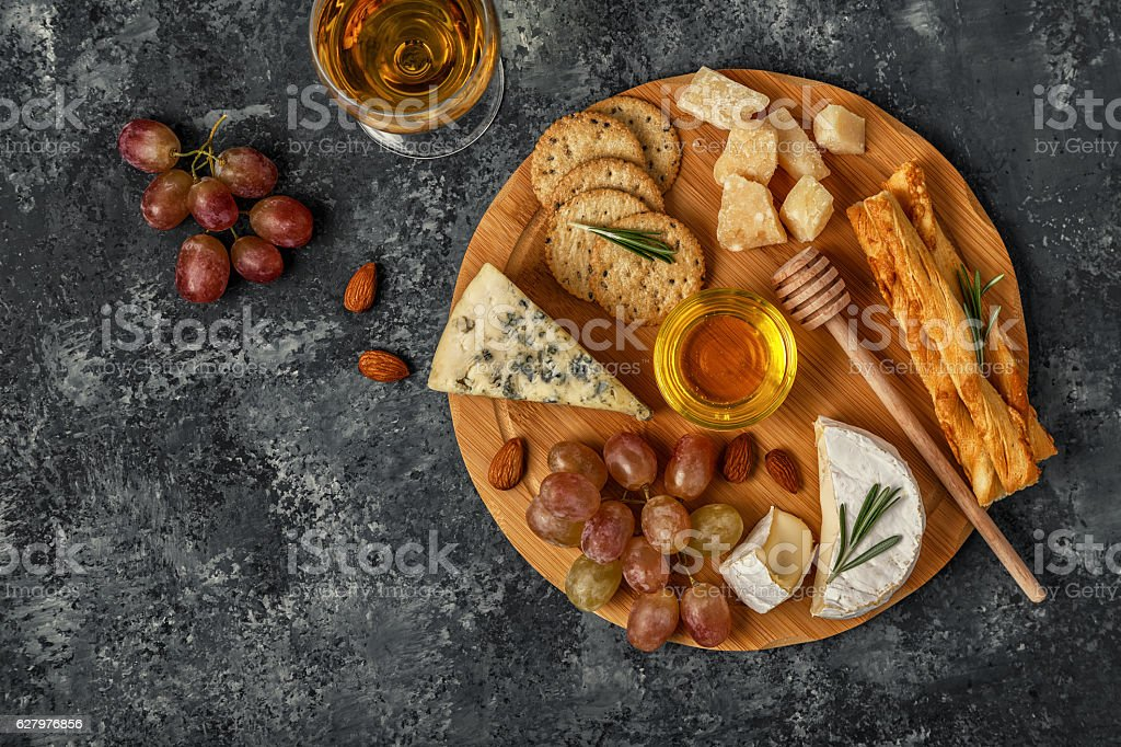 Assortment of cheese with wine, honey, nuts and grape stock photo