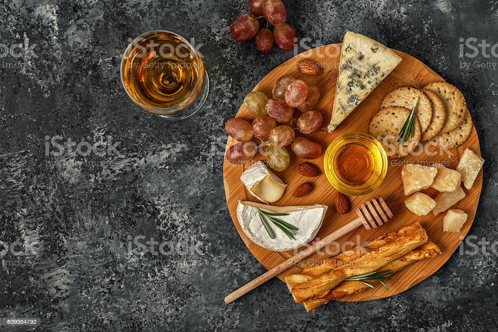 Assortment of cheese with wine, honey, nuts and grape. stock photo