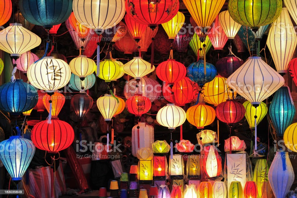 Assortment of colorful Asian lanterns lit up in a dark room royalty-free stock photo
