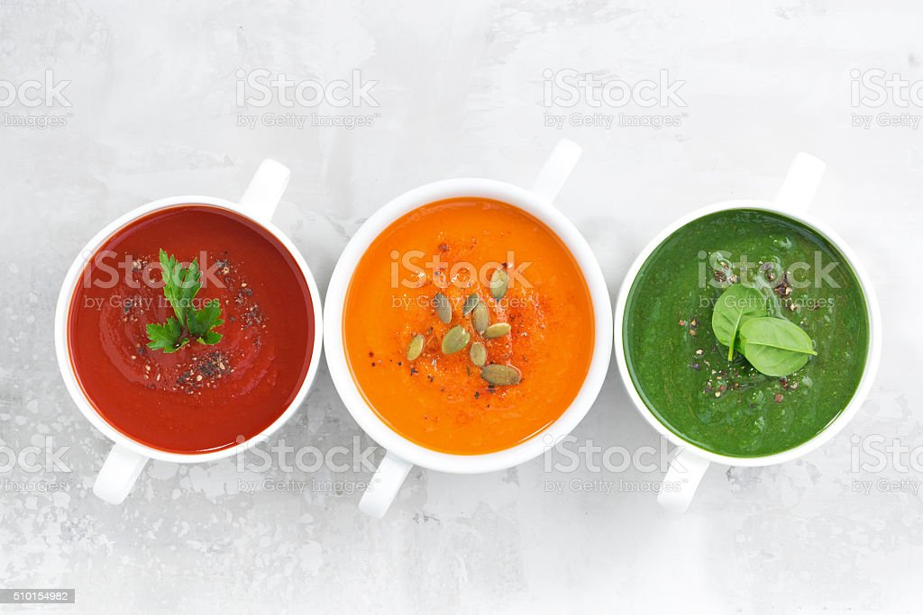 assortment of colorful vegetable cream soup on white background stock photo