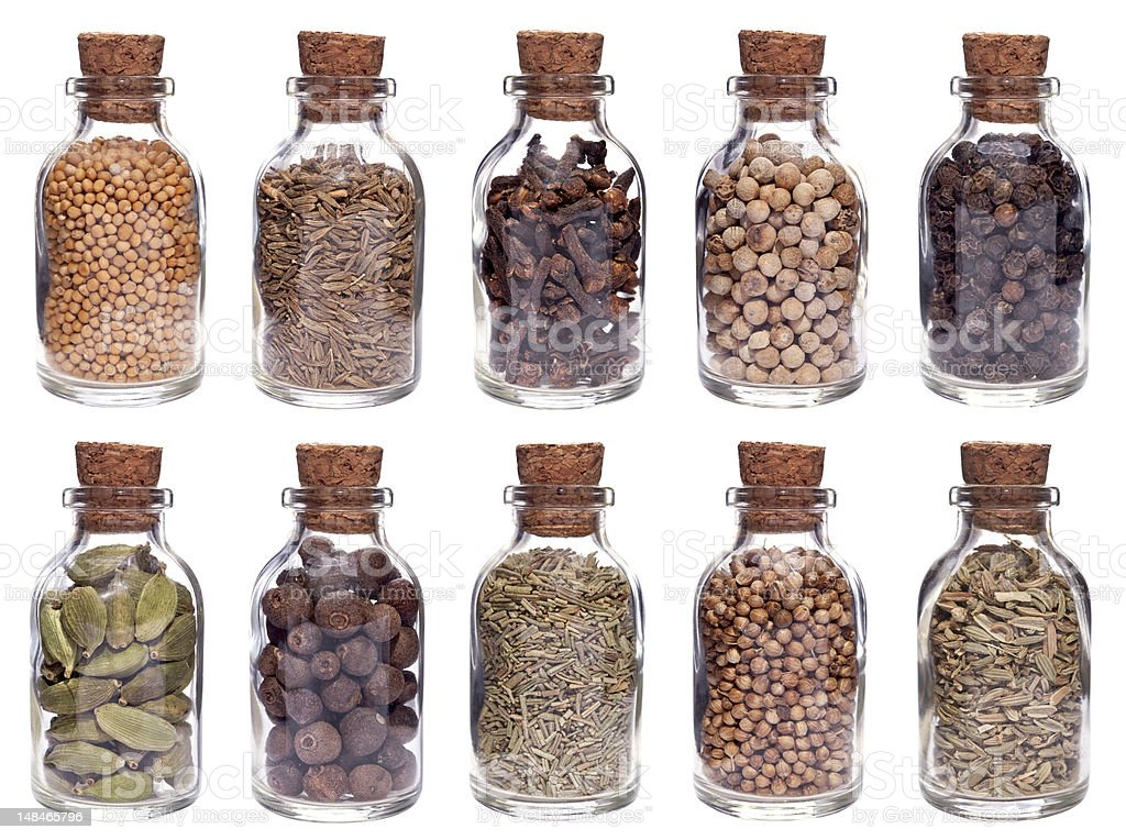 Assortment of different spices in glass bottles isolated on white royalty-free stock photo