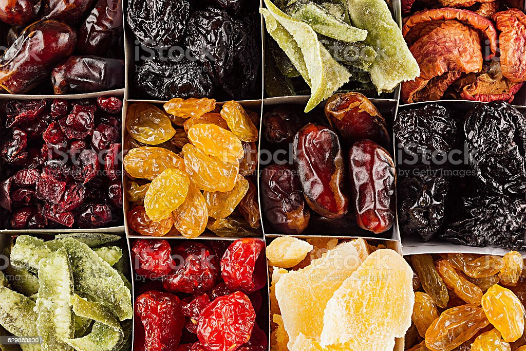 Assortment of dried fruits closeup background in square cells. stock photo