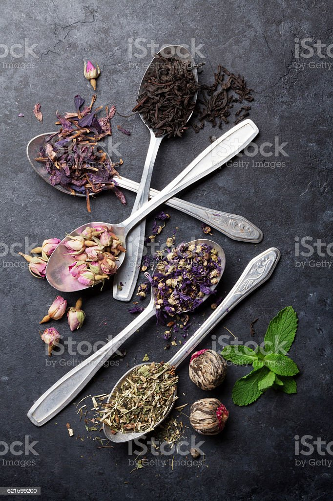 Assortment of dry tea in spoons stock photo