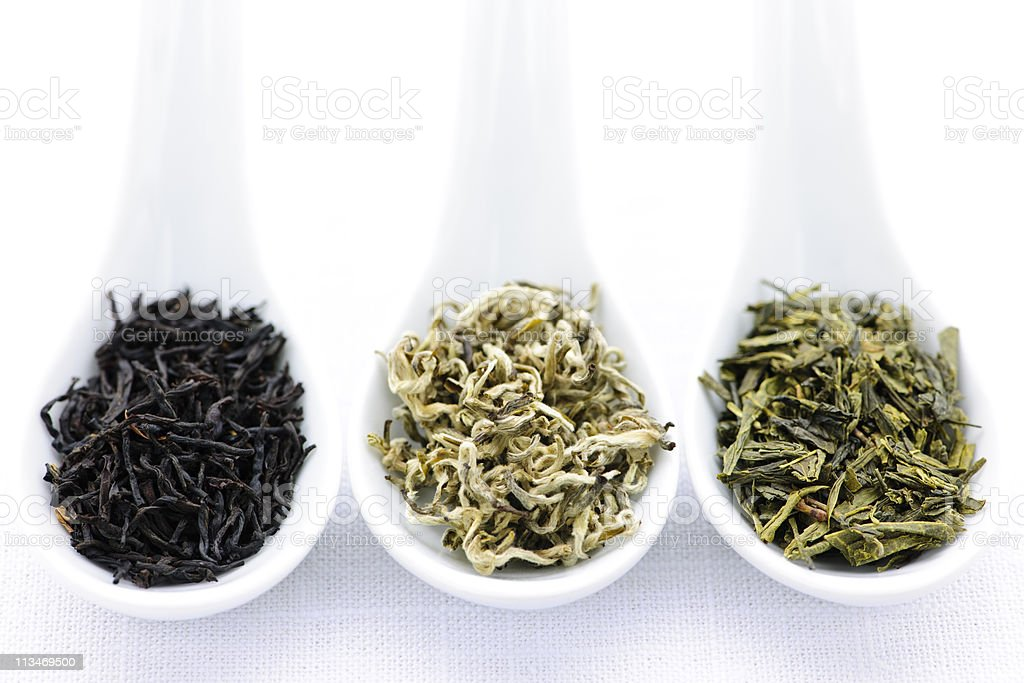 Assortment of dry tea leaves in porcelain spoons stock photo