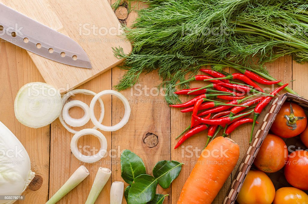 Assortment of fresh vegetables close up with cutting board stock photo