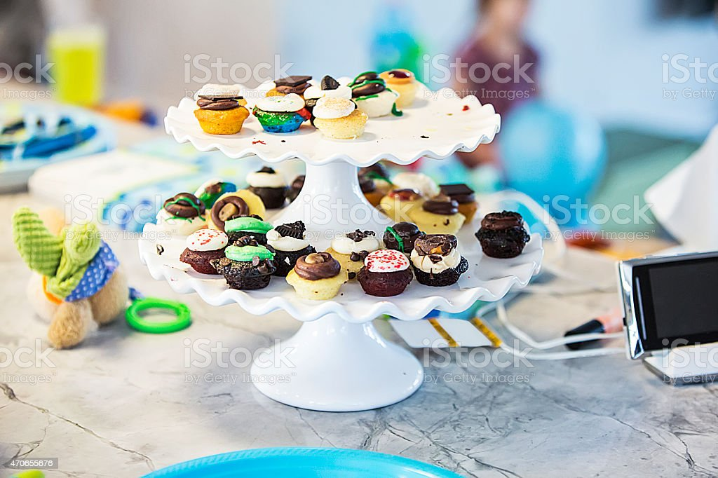Assortment of mini cupcakes on two tiered round platter stock photo