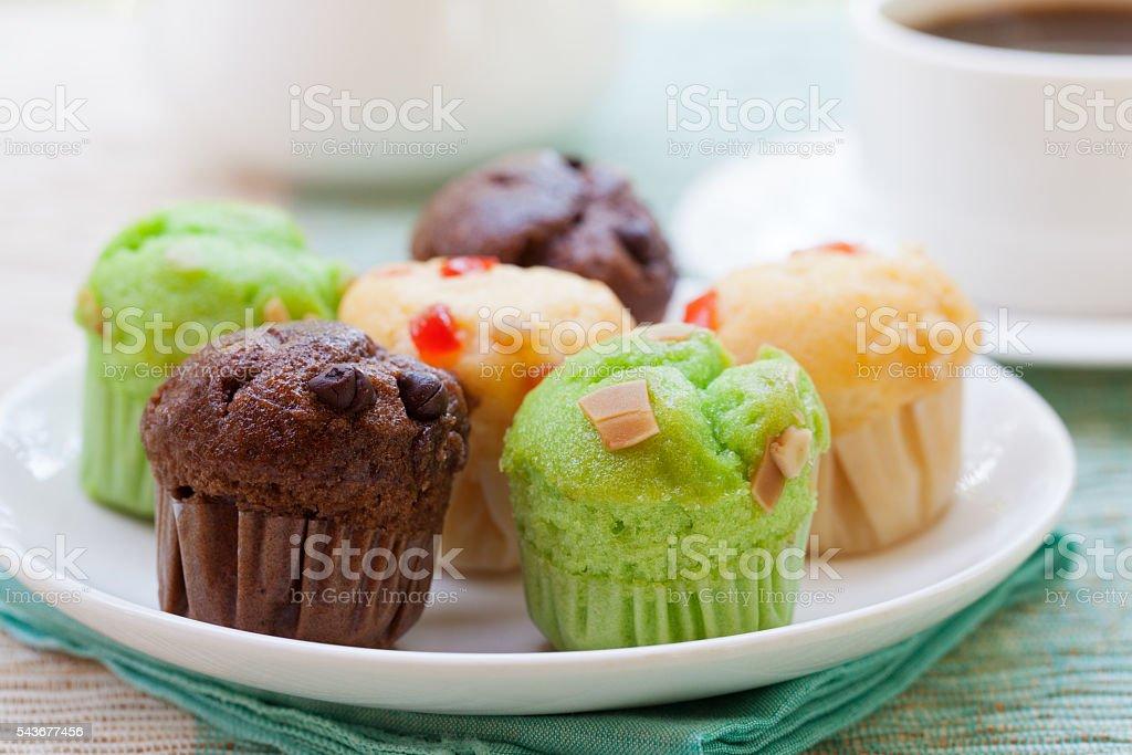 Assortment of muffins vanilla, chocolate, pandan on a white plate. stock photo