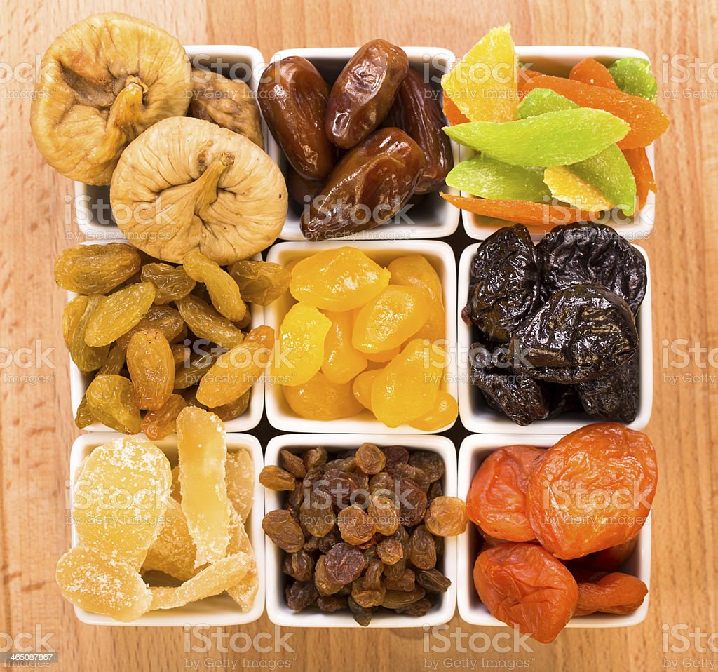Assortment of nine dried fruits on a wooden table stock photo