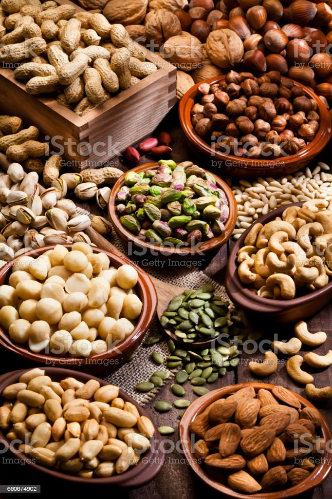 Assortment of nuts on rustic wood table. stock photo