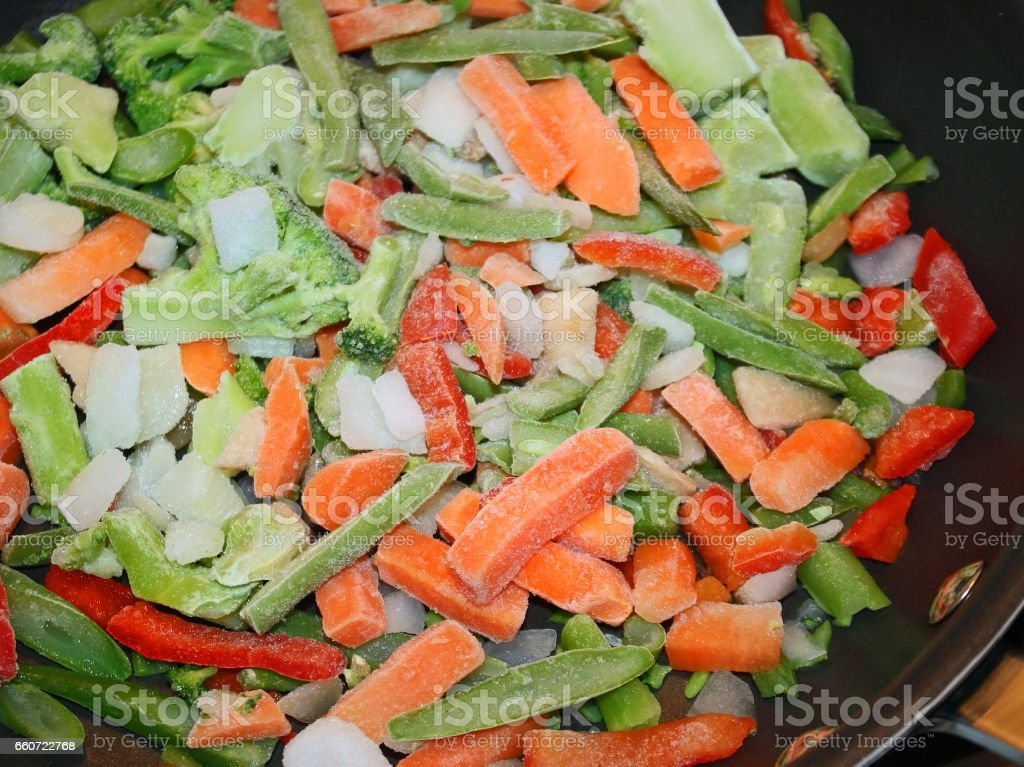 Assortment of raw frozen vegetables in non stick skillet ready for cooking stock photo