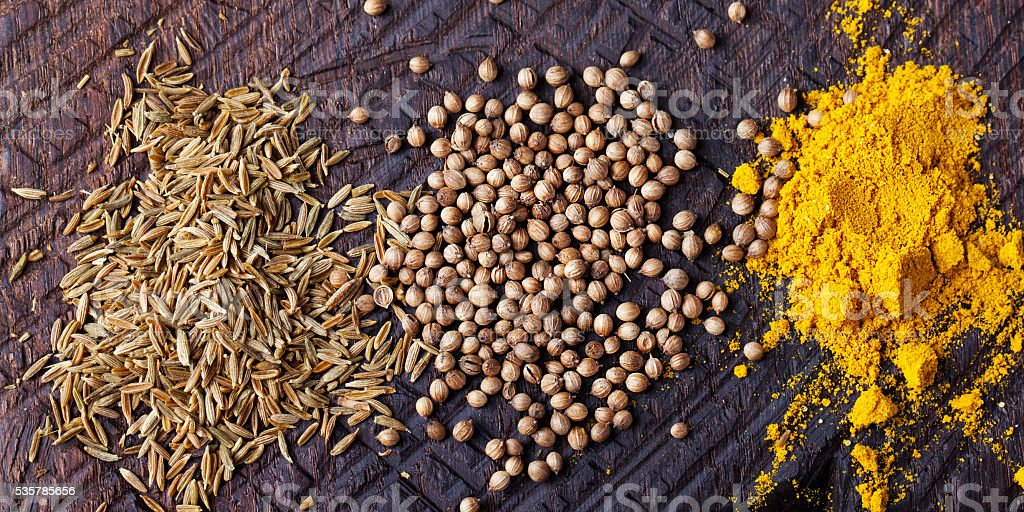 Assortment of spices. Cumin, carry, turmeric, coriander on cutting board stock photo