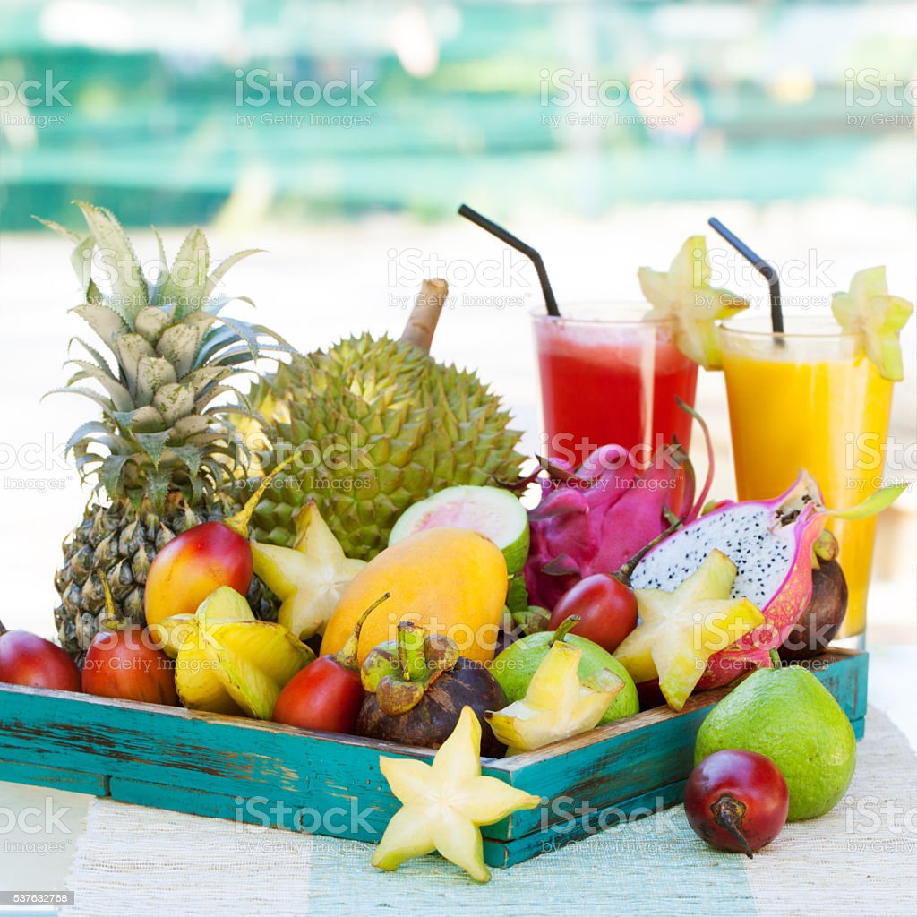 Assortment of tropical exotic fruits with smoothie and fresh juice stock photo