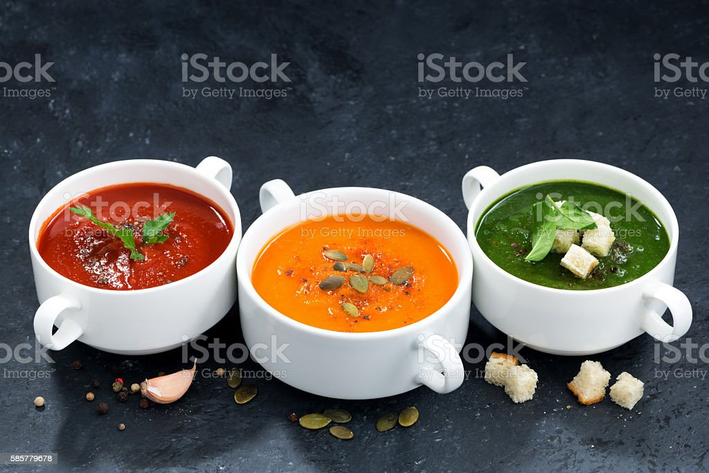 assortment of vegetable cream soup on a dark background stock photo