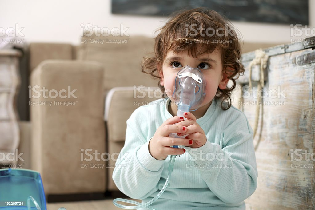 Asthma, little girl with inhaling mask stock photo