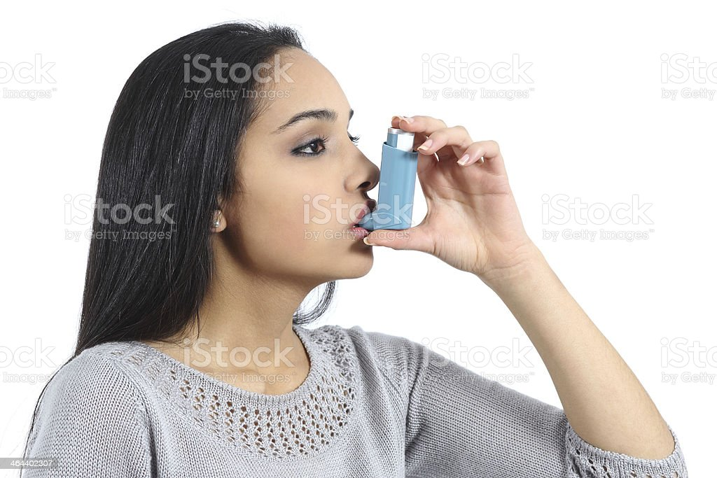 Asthmatic arab woman breathing from a inhaler stock photo