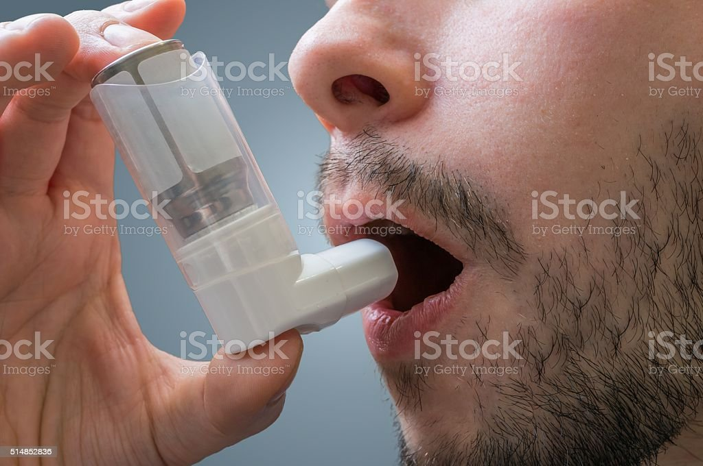 Asthmatic man suffers from asthma and is using inhaler. stock photo