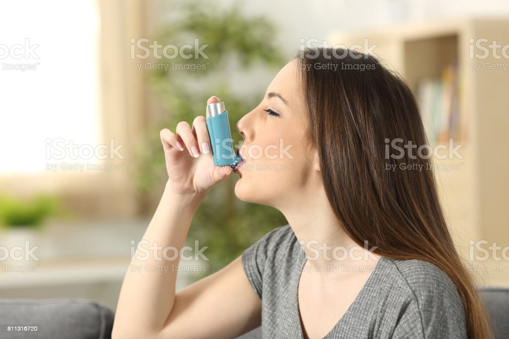 Asthmatic woman using an inhaler stock photo