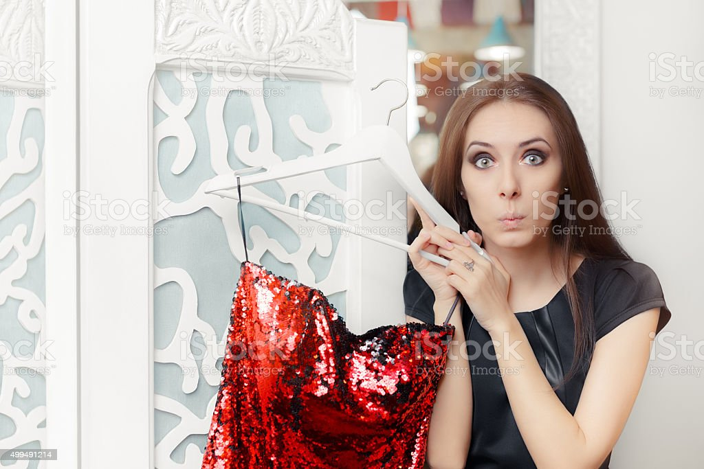 Astonished Girl Trying on Red Party Dress in Dressing Room stock photo