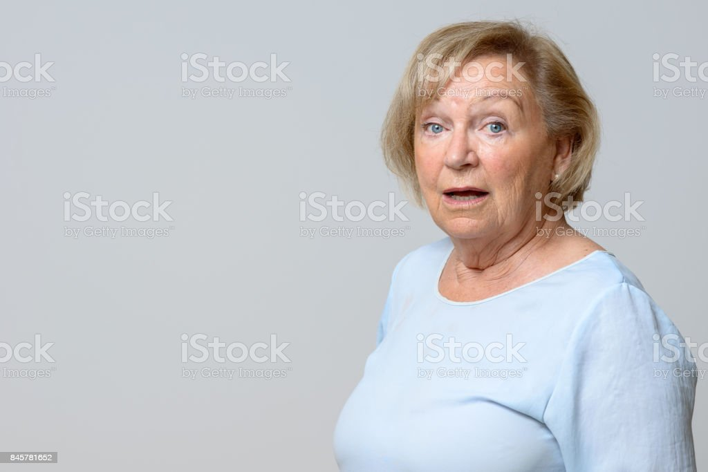 Astonished senior woman looking at the camera stock photo