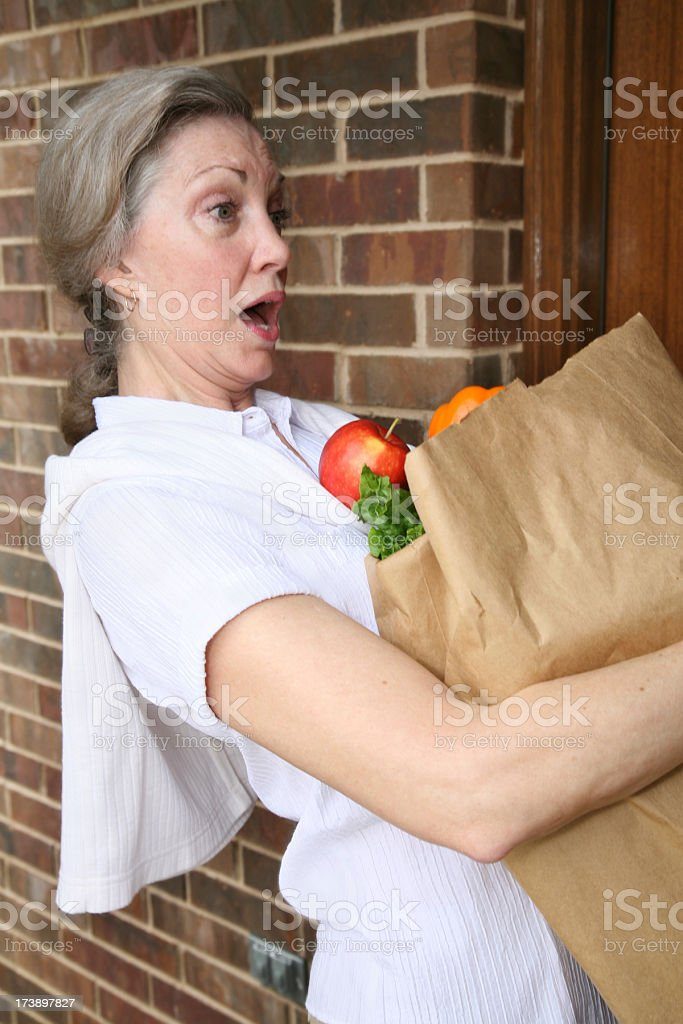 Astonished Woman Spilling Her Grocery Bag royalty-free stock photo