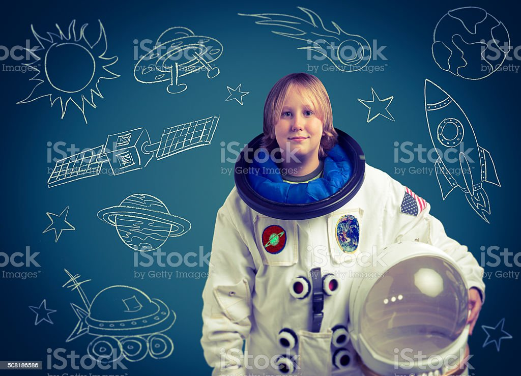 Astronaut Child in Front of Chalkboard Outer Space Drawings stock photo