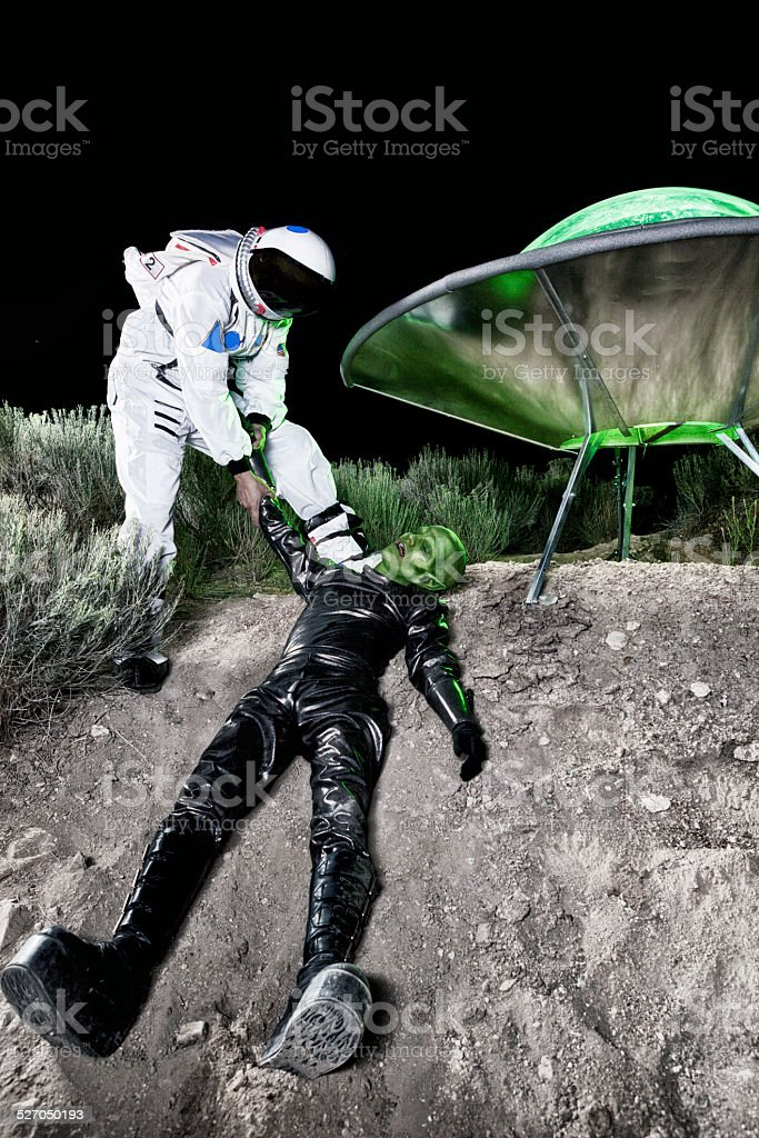 Astronaut Dragging Alien at Landing Site stock photo