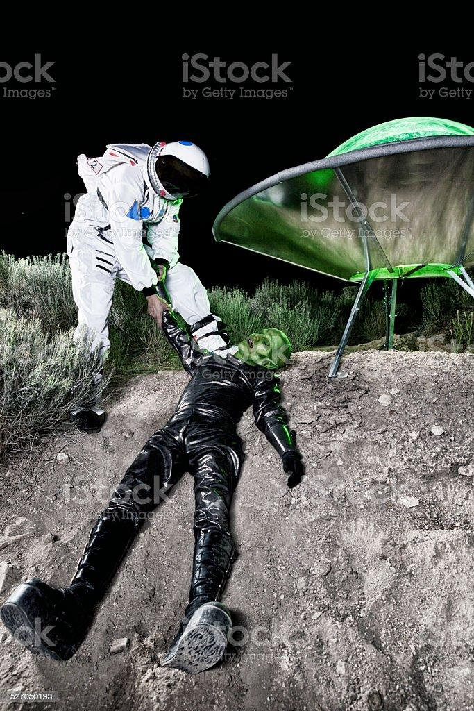 Astronaut Dragging Alien at Landing Site stock photo