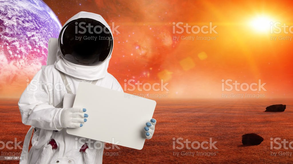 Astronaut In Space Holding A Sign On Alien Planet stock photo