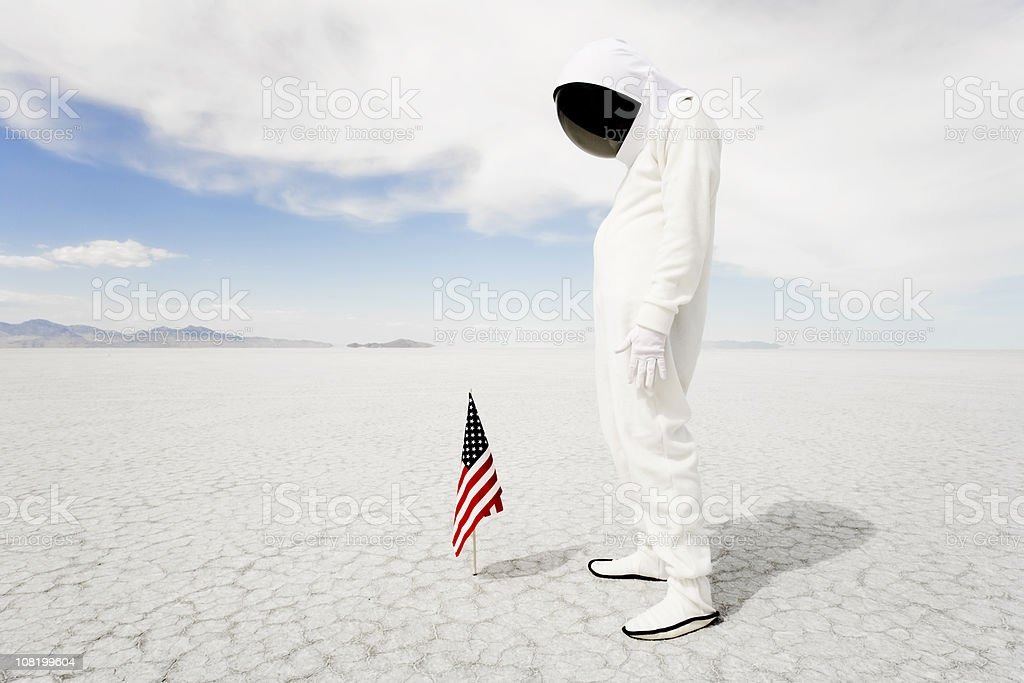 Astronaut Looking at American Flag stock photo
