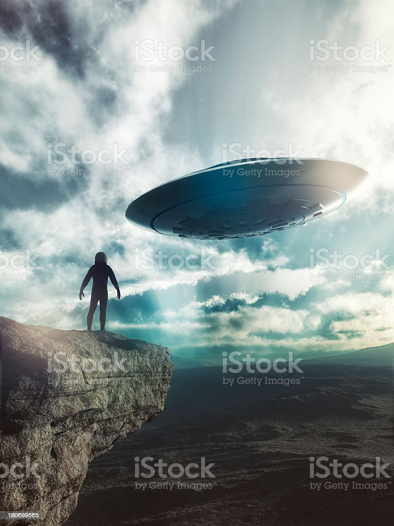 Astronaut on distant planet discovering UFO stock photo