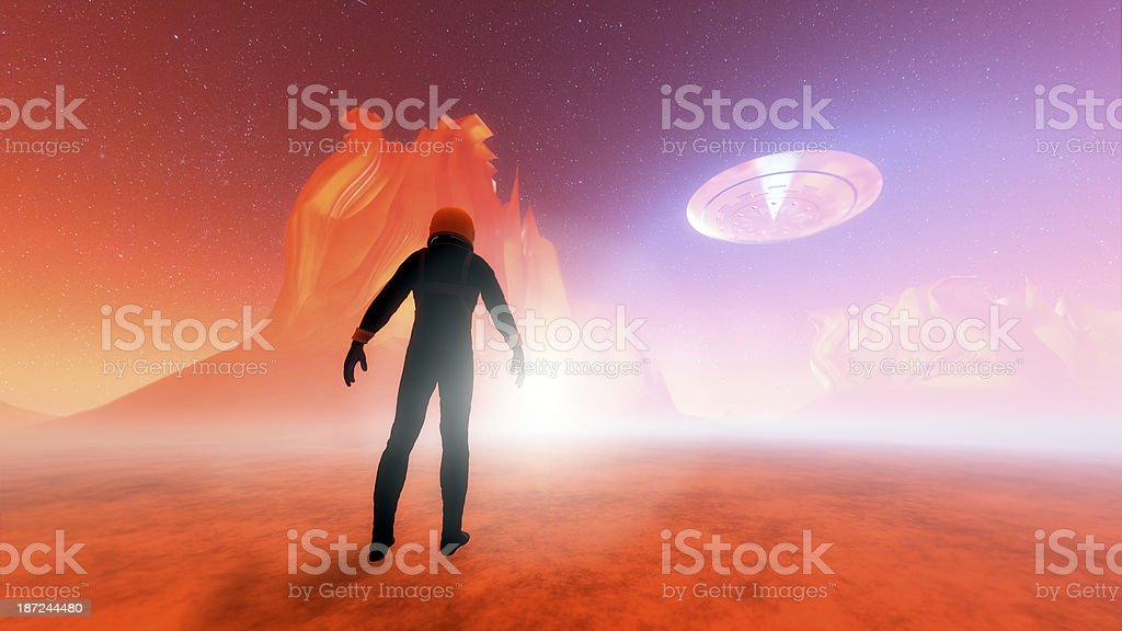 Astronaut on distant planet discovering UFO royalty-free stock photo