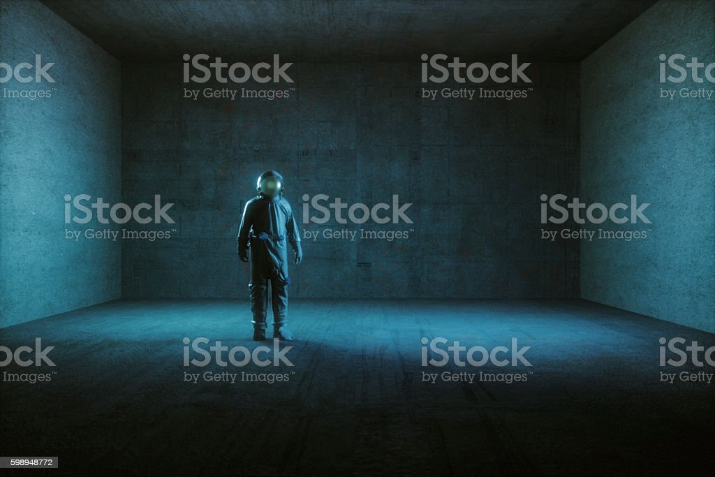 Astronaut standing in empty spaceship room stock photo