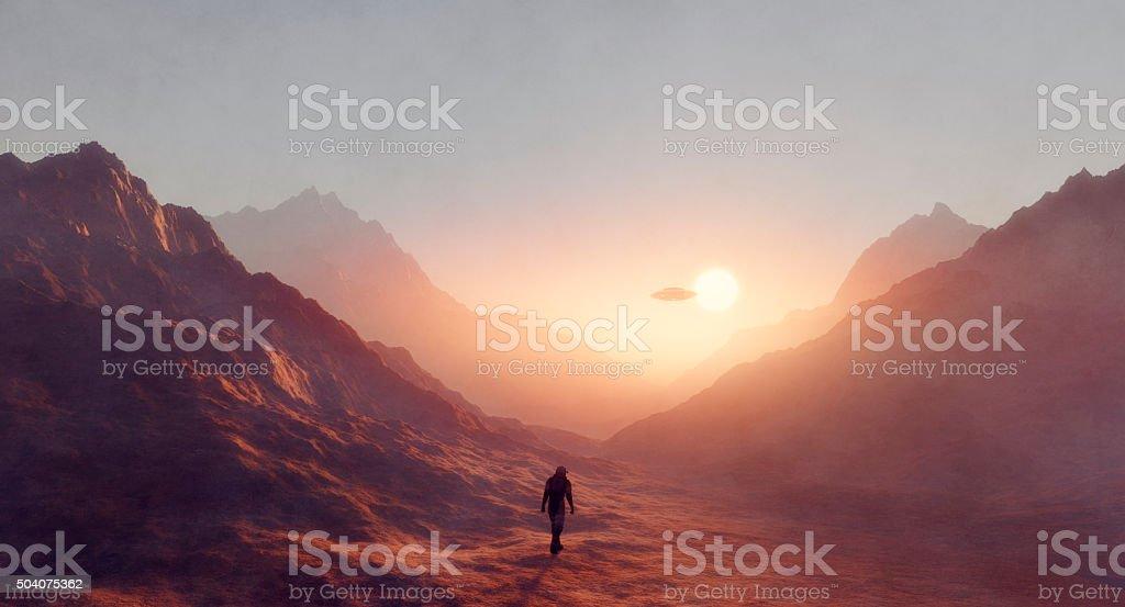 Astronaut walking on Mars, UFO flying stock photo