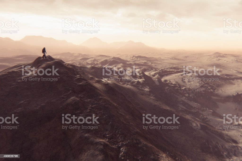 Astronaut walking on smaller Martian mountain ridge stock photo