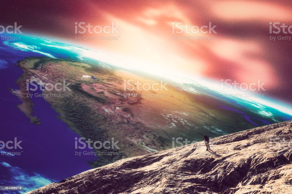 Astronaut walking on the Moon observing Earth stock photo
