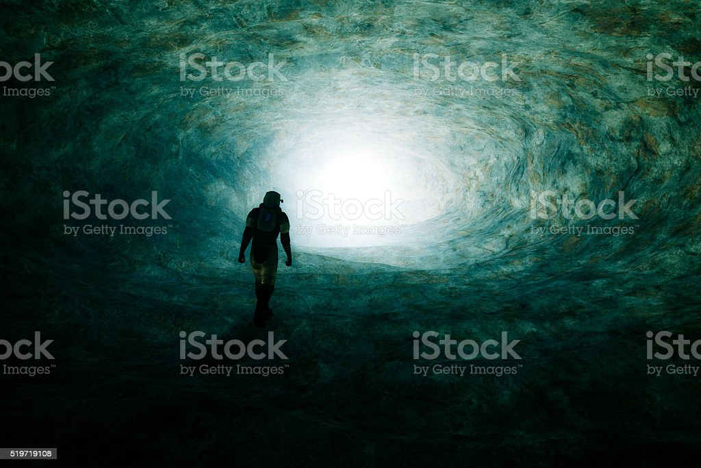 Astronaut walking towards mysterious light stock photo