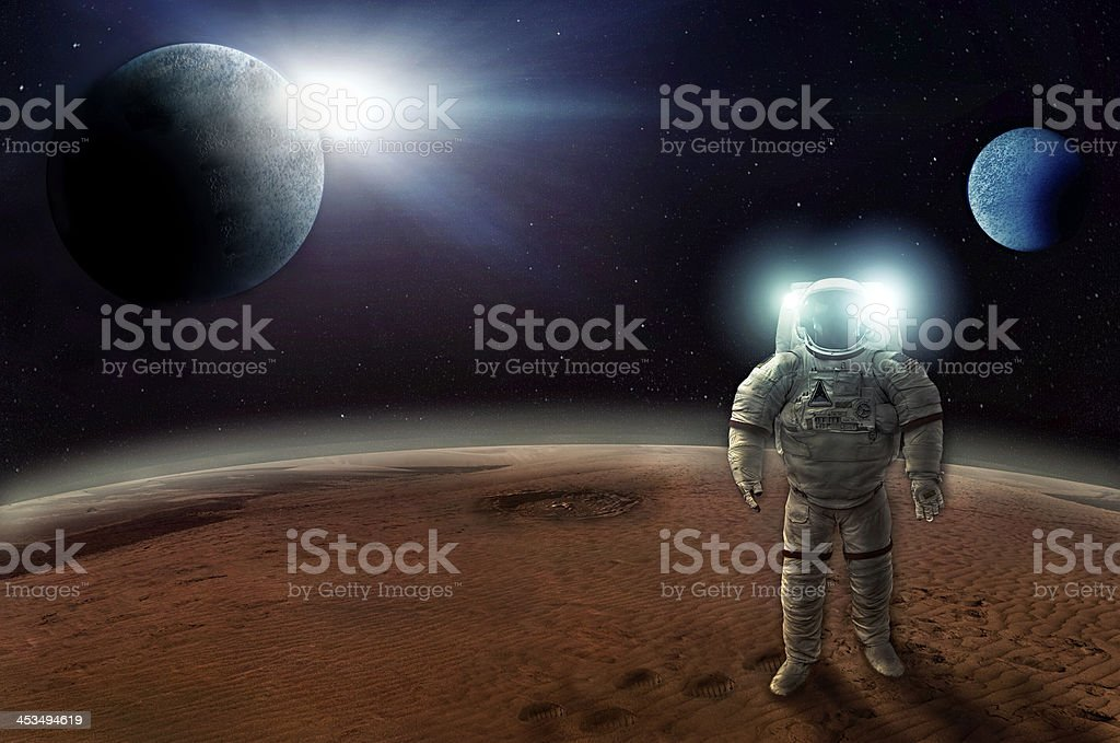 Astronaut walks alone on the surface of a planet stock photo