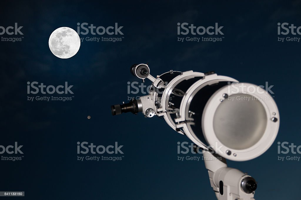 Astronomical telescope over dark sky with the moon stock photo