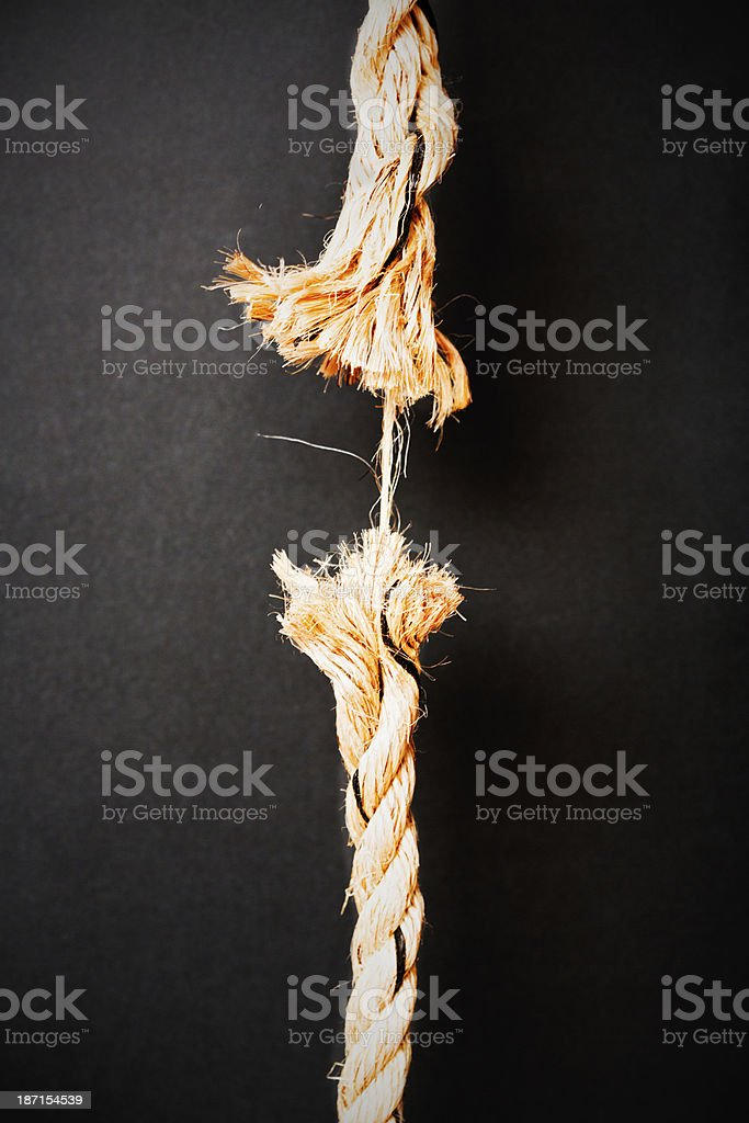 At breaking point, rope is frayed to last strand stock photo