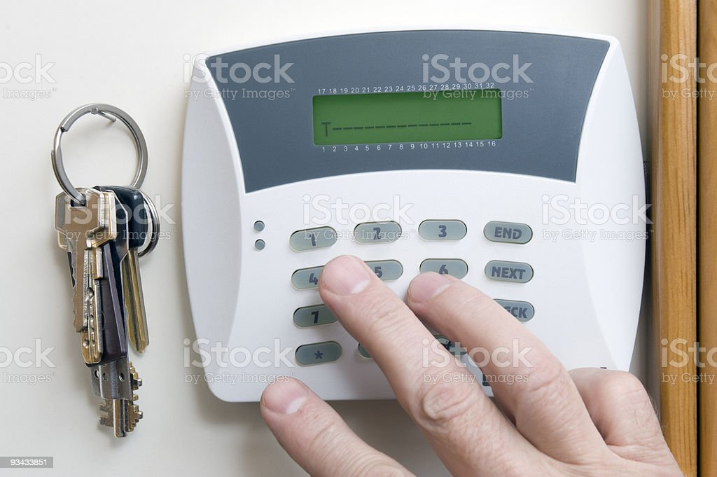 At set of keys hang next to a burglar alarm on the wall royalty-free stock photo