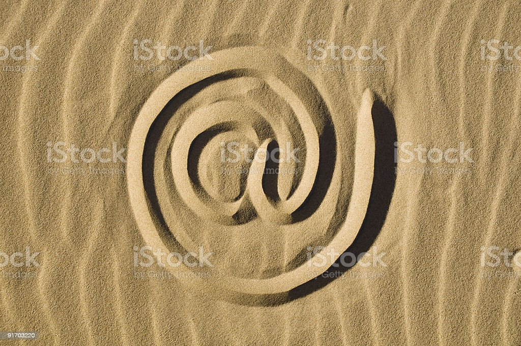 At sign drawn in the sand stock photo