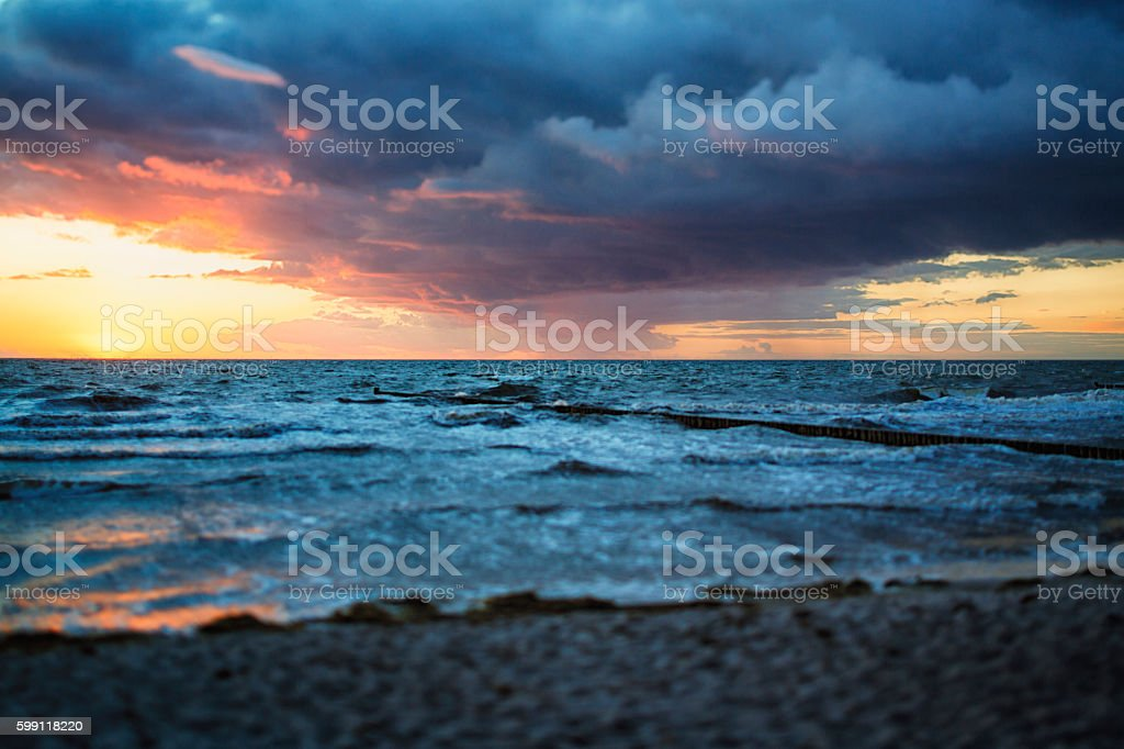 At the ocean after storm in sunset stock photo