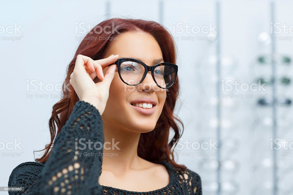 At the optician young woman chooses  glasses   Ophthalmology   Optical store stock photo