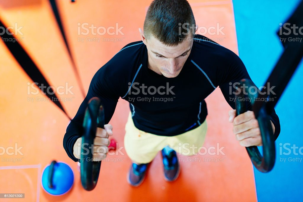 athlede doing chin ups on gymnastic rings during cross training stock photo