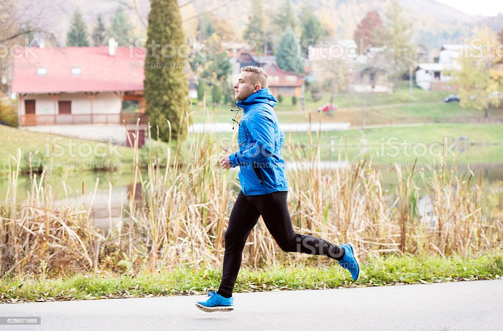 Athlete at the lake running against colorful autumn nature stock photo